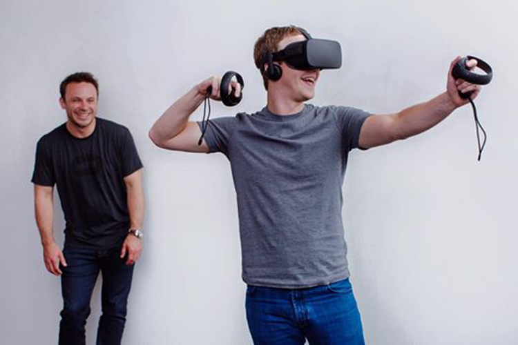 Mark Zuckerberg tests out the new Oculus touch hand controllers as Brendan Iribe observes